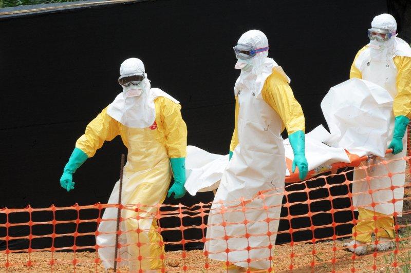 Médicos carregam o corpo de uma vítima mortal do vírus. foto: Seyllou/AFP/Getty Images